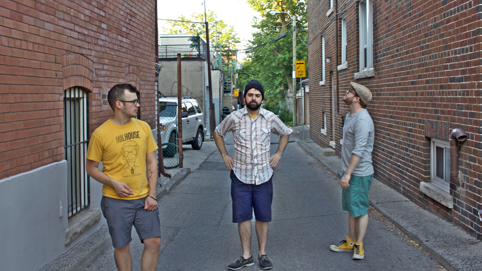 stephen, jake, and pat stand a few feet apart, not looking at the camera, with an alley stretching on behind them