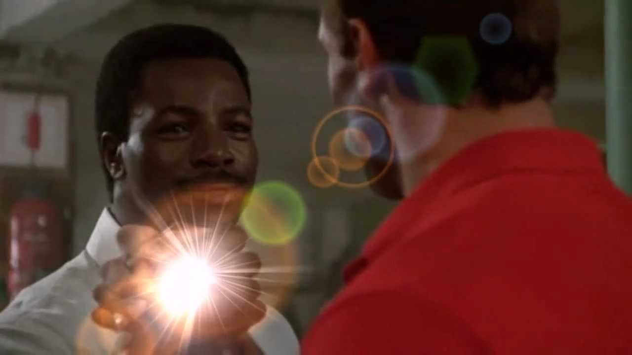 a bright flash of lens flare glows over the locked fists of carl weathers and arnold schwarzenegger as they arm wrestle upon greeting each other in the movie predator