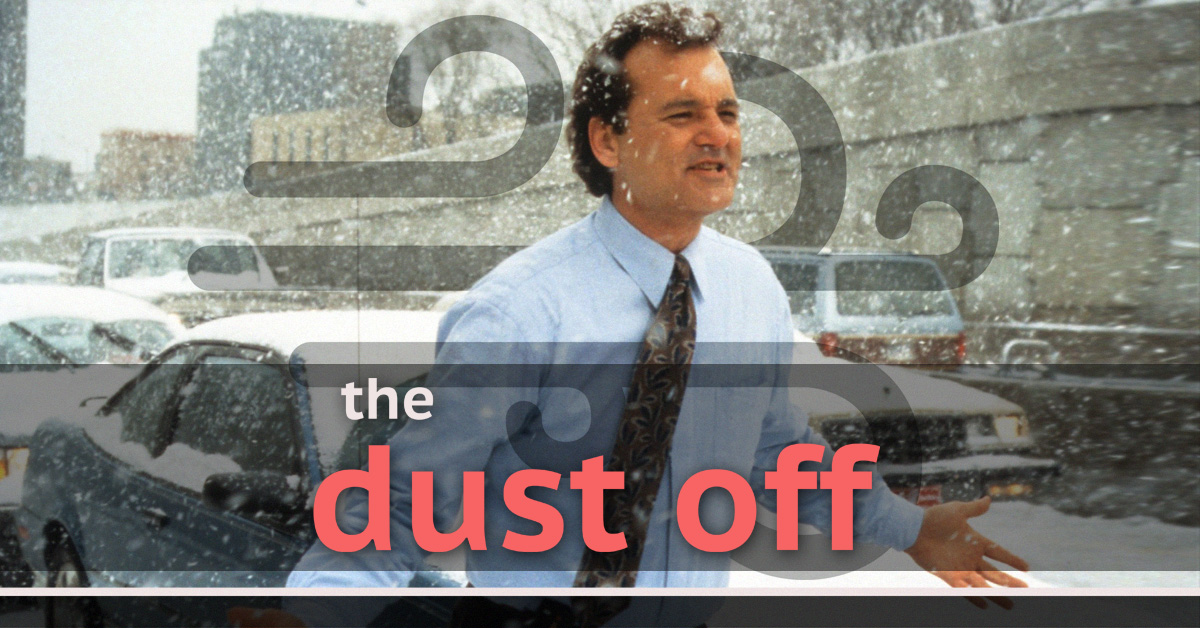 Bill Murray shrugs while walking in a blizzard in a shirt and tie